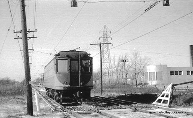 "The ""mystery photo."" A TM or Speedrail 1100 poss. 1142 is running backwards EB on the eastbound track at Sunny Slope Rd. J.G. Van Holten plant at right. Collection of C.N. Barney."