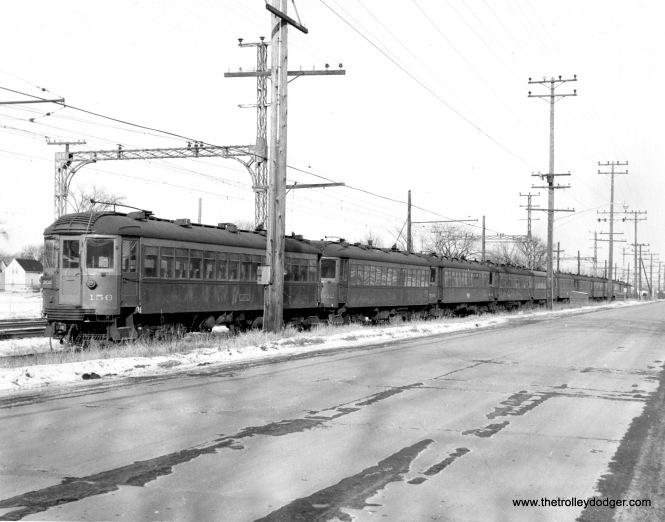 North Shore Line 156 and several others at Waukegan in December 1962. Since there are about a dozen cars visible, they are being stored on a siding which you will note is outside the area of the catenary. (George Niles, Jr. Photo)