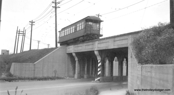 "This picture was taken on the Evanston branch of the ""L"", and the wooden ""L"" car is signed ""Howard Only,"" which suggests this was taken during the CTA era. Previously, all Evanston trains continued south into the city. The nearby curve would indicate that this picture was taken just north of Howard, and may show the viaduct where the line crossed Chicago Avenue, which is a continuation of Clark Street."