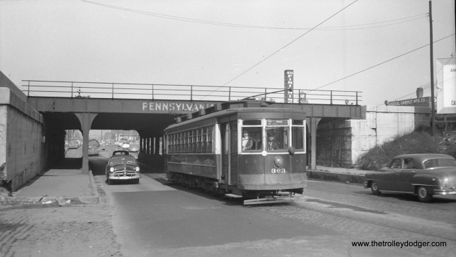 "CTA 363 at the Pennsylvania Railroad viaduct at Ashland and Arbor in March 1951. Andre Kristopans notes, ""363 Ashland north of Fulton – bridge has three railroads over it, closer behind car is PRR with Milwaukee Road also using the same tracks, beyond is C&NW. Note that street under bridge is much narrower than rest of street. Ashland was widened relatively late, and the bridges were never widened out to this day."""