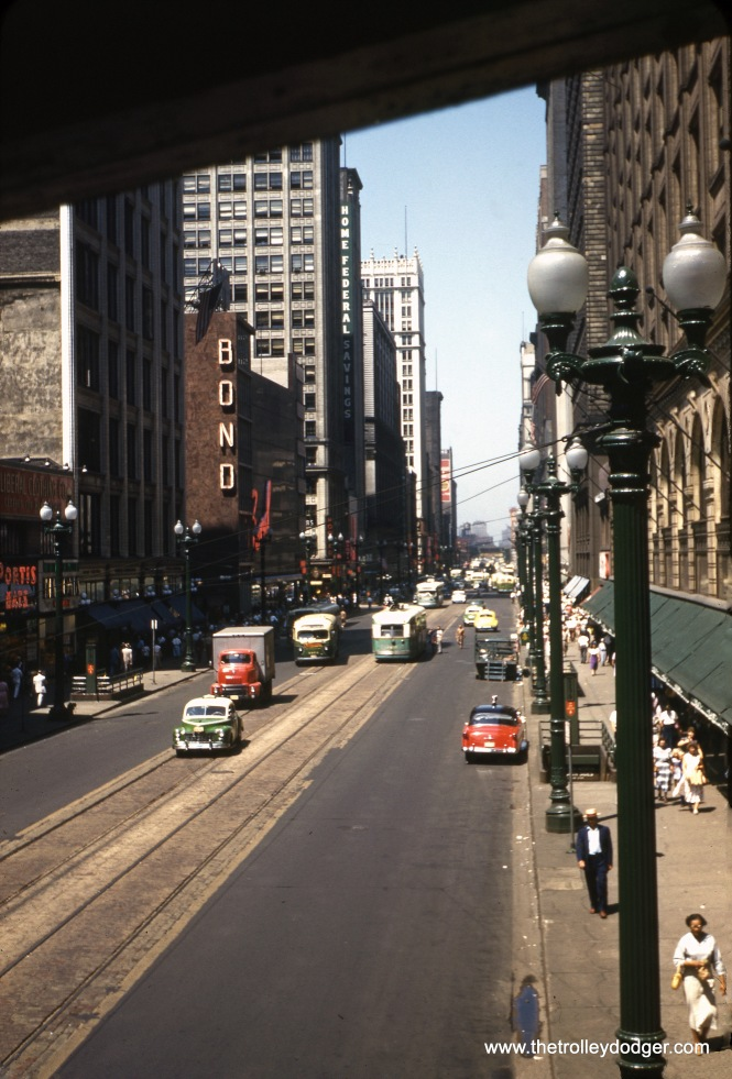 "On July 4, 1953, we are looking north from the stairway to the CTA's ""L"" station at State and Van Buren. Streetcars are still running on State Street, via tracks laid in concrete about ten years before when the State Street subway was built. The nearby subway entrances are in their original configuration. State did not get those ""preying mantis"" street lights until 1959."