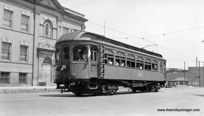 "Chicago North Shore and Milwaukee wood car 300 on a fantrip on the streets of Waukegan circa 1940. From 1939 until 1942, the North Shore Line allowed Central Electric Railfans' Association to use 300 as their ""club car."" Here, we see it parked in front of Immaculate Conception school."