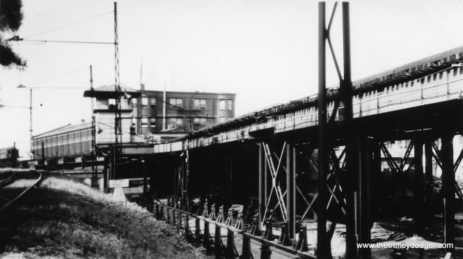 "This view looks north towards the Wilson ""L"" yard and shops. You can see the interlocking tower, and at left, part of the ramp down to Buena Yard, which was used for freight. Dan Cluley writes, ""Looking at the Wilson Shops photo, am I correct that those are some of the piggyback flat cars in between the grass and the L structure?"" I asked an expert. Here's what J. J. Sedelmaier says: ""It's absolutely the NSL Ferry-Truck equipment! That's the old Wilson Shops building in the background and that's the north end of Montrose Yards and transfer station."""
