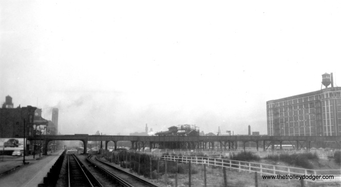 "Here, we are looking east along Van Buren, just west of Paulina. The tracks in the foreground are the temporary Garfield Park ""L"" right of way. The Congress (later Eisenhower) expressway is under construction to the right, with the Douglas Park ""L"" in the background. This photo was probably taken in early 1954. The Garfield Park ""L"" west of Paulina has already been demolished, but the Marshfield station still appears intact. This could not be removed until the Douglas line was re-reouted over the Lake Street ""L""."