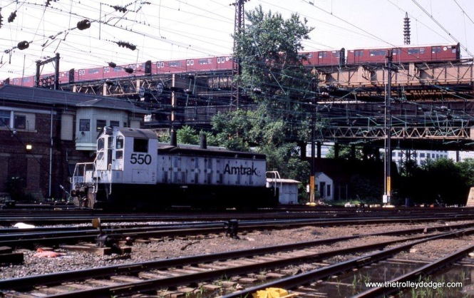 "I wanted to include this photo in spite of the fact that the subject is Amtrak SSB-1200 #550 at Q Tower at Sunnyside, Queens, New York. I hope it will be of interest to traction fans because of the IRT subway train of NYCTA R-36 ""Redbirds"" passing overhead in the background. 6-20-87."