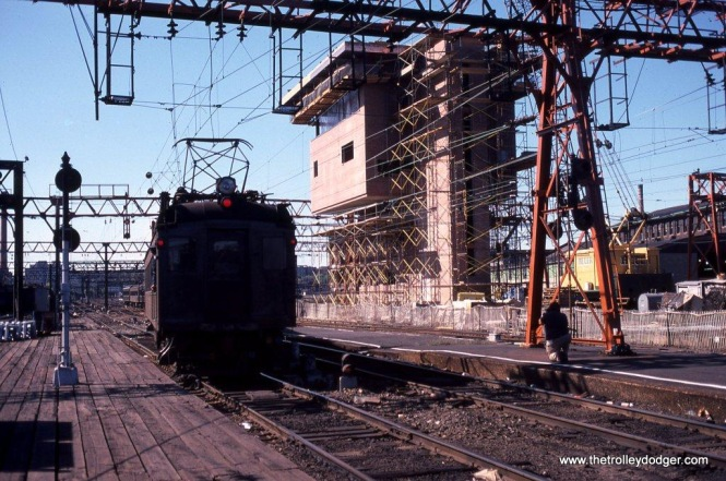 Photo 14. Big changes are coming! In 1982, along with the work to convert the 3000 Volt DC current to 25,000 volt 60 hertz AC, NJT was building a new TERMINAL tower. A train of MUs depart Hoboken passing the new tower still under construction.