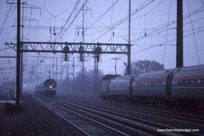 Photo 22. Amtrak AEM-7s 926 & 929 meet at speed in the rain at the Jersey Avenue station in New Brunswick, NJ. November 1991.