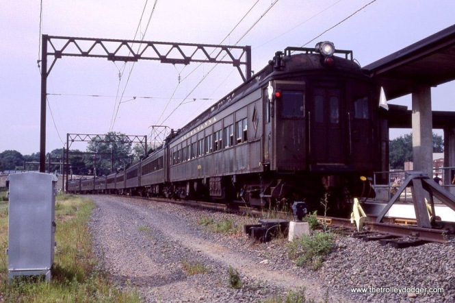 "Photo 24. Just before the end of DC operation, the Tri-State chapter of the National Railway Historical Society organized a ""farewell"" excursion of the Ex-DL&W MUs. Polar car #3454 carried the white EXTRA flags at a photo stop at Bay Street Station, Montclair, NJ on August 19, 1984."