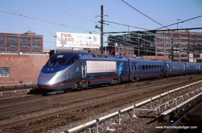 Photo 36. Amtrak Acela power car #2028 and a PATH train of PA-3 & PA-4 cars at Harrison NJ.