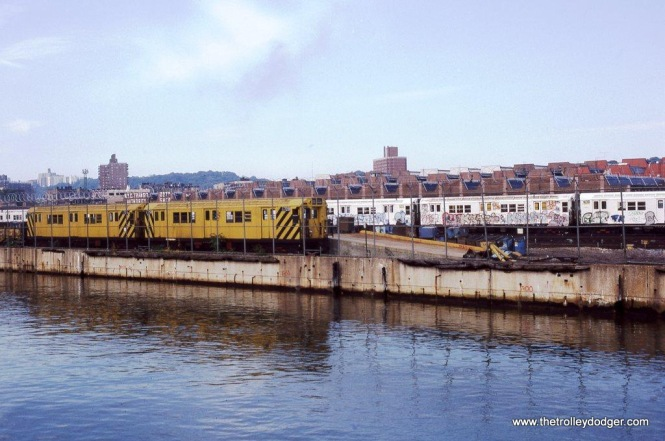 The NYCTA Car Repair yard at 207th Street in New York as seen from a boat in the Harlem River in 1986. Visible just behind the fence are two R-21 garbage motors. These cars were tasked with the removal of trash from the subway. The two shown here G7208 and G7206 have both been retired and most likely scrapped.