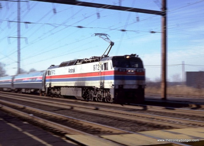 "Photo 7. Amtrak E-60C #972 speeding through Edison, NJ in December of 1979. I couldn't stop the fast motion of the trains with the camera I had, so I decided to try to make the best of it by using the motion blur to convey a sense of speed and power. This is one more of only a few of the ""blur"" shots that I actually like."