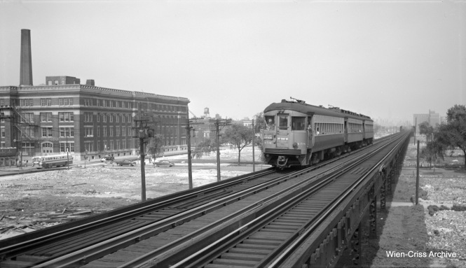 "CA&E 458 heads a three-car train westbound at Western Avenue. The CTA bus on Van Buren indicates that this picture was taken no earlier than August 12, 1951. The Van Buren Street temporary trackage appears to be in place already, but testing has not started yet, as there are barriers in place. ""L"" service shifted to the temporary trackage in September 1953 and the CA&E cut back service to Forest Park. At left you can see the imposing structure of Richard T. Crane Medical Preparatory High School, otherwise known as Crane Tech. We are looking to the east. (Robert Selle Photo, Wien-Criss Archive)"