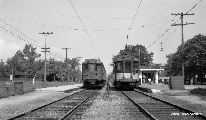 Two North Shore Line trains pass at Ravinia on a 1953 Shore Line Route fantrip. This is not the same stop as Ravinia Park, which is some distance away. The area taken up by the NSL tracks is now a parking lot for the Metra station (former Chicago & North Western), whose tracks are at left. We are looking southeast. Presumably the Silverliner at right is the fantrip train as the other train is not flying flags. (Robert Selle Photo, Wien-Criss Archive)