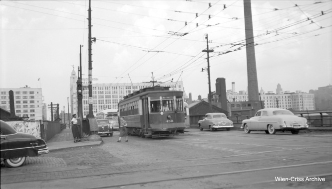 CTA Pullman 453 is heading west on diversion trackage on Route 8 - Halsted at Chicago Avenue in 1953. I believe the PCC at the rear is 7228, a product of the St. Louis Car Company. The diversion was between Division and Chicago, and was used when work was being done on the Halsted Street bridge over the Chicago River. The two streetcars are about to turn from eastbound Chicago Avenue onto southbound Halsted. PCCs were being phased out on Halsted during this period, as CTA had begun shipping the 310 Pullmans to the St. Louis Car Company for scrapping and parts reuse on a like number of 6000-series rapid transit cars. By the time streetcar service ended on Halsted in 1954, service was being provided entirely by the older red cars. (Robert Selle Photo, Wien-Criss Archive)