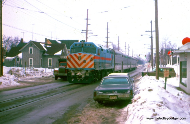Michigan City, Indiana: loco #109 powers a westbound CSS&SB train (made up of RTA-owned equipment) as it heads westbound in 11th (having just made its Michigan City passenger stop). View looks west from Franklin Street, February 1982. (William Shapotkin Photo)