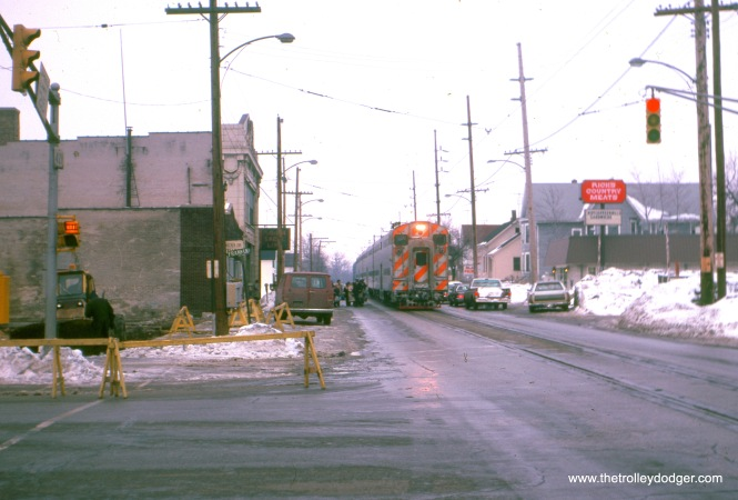 Michigan City, Indiana: a westbound South Shore Line passenger train (made up of RTA-owned equipment) is westbound in 11th Street, arriving at the Michigan City passenger station. The view looks east across Franklin Street, February 1982. (William Shapotkin Photo)