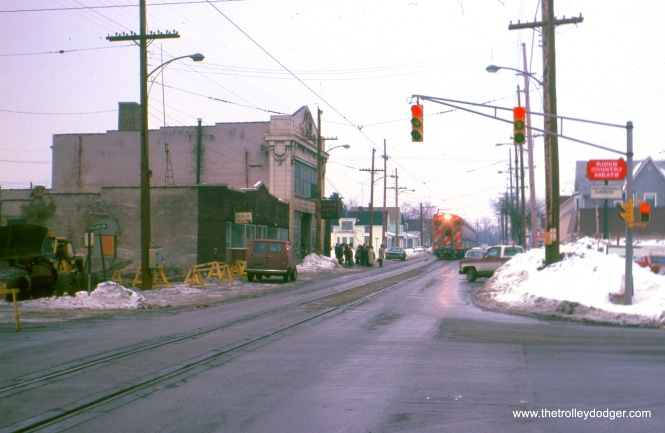 Michigan City, Indiana : A westbound South Shore Line train (made up of RTA-owned equipment, and powered by loco #1097, is westbound in 11th Street, arriving at the Michigan City passenger station. The view looks east across Franklin Street, February 1982. (William Shapotkin Photo)