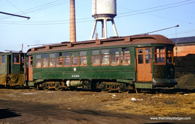 "This ""red border"" Kodachrome shows CTA salt car AA-104 at South Shops on January 4, 1956. Don's Rail Photos says, ""AA104, salt car, was built by South Chicago City Ry in 1907 as SCCRy 339. It was rebuilt in 1907 and became C&SCRy (Calumet and South Chicago Railway) 838 in 1908. It was renumbered 2853 in 1913 and became CSL 2853 in 1914. It was later converted as a salt car and renumbered AA104 in 1948. It was retired on December 14, 1956."" This was one of the few railroad-roof cars on the Chicago system. The main color here is Pullman Green. (James J. Buckley Photo)"