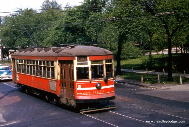 """Chicago, IL. CTA car #3153, working an eastbound trip on Route 16 - Lake, is eastbound in (North) Lake Street, having just crossed over Central Avenue. View looks west/northwest from the Chicago & North Western embankment. May 15, 1954."""