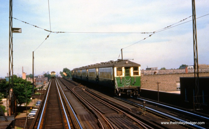 """Chicago, IL. CTA car #4333 brings up the rear of an eastbound Lake Street ""L"" train. View looks east from Lake/Laramie station. Note pull-offs for overhead trolley wire, used west from Laramie station. June 23, 1959,"""