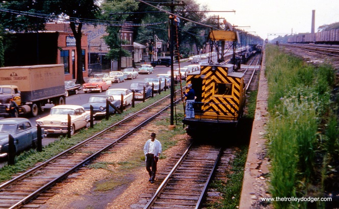 """Chicago, IL. Looking westbound on CTA's Lake Street ""L"" at (South) Lake Street (now Corcoran Place), at Menard Avenue. Line car #S200 is seen doing wire work. In distance is the Austin/Lake ""L"" station. At right (on embankment) is one-time ""Boulevard"" Chicago & North Western station (located at Austin Boulevard). May 27, 1960."" Don Ross: ""S-200 was built by Barney & Smith in 1901 at M-WSER 783. It was renumbered in 1913 as 2783. In 1916 it was rebuilt as a work motor and numbered S-200. It became CRT S-200 in 1924."""