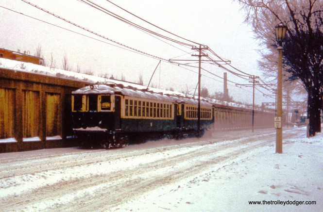 """Oak Park, IL. A pair of 4000s, working a westbound trip on CTA's Lake Street ""L"", are on South Boulevard at Kenilworth Avenue. Visible in distance (on embankment) is one-time ""Avenue"" Chicago & North Western passenger station, located at Oak Park Avenue. View looks east on January 18, 1962."""
