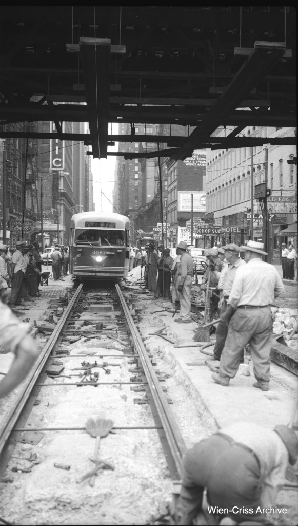 "CTA PCC 4081, heading south on Route 22 - Clark-Wentworth, proceeds slowly through a work zone at Clark and Van Buren on July 17, 1954. For more pictures of this, see our previous post Track Work @Clark & Van Buren, 1954 (February 1, 2015). This negative was apparently sold by an ""RJA"" at one point, which may mean the photo was taken by railfan Richard J. Anderson. This track work was related to the conversion of Clark and Dearborn into one-way streets downtown. (Wien-Criss Archive)"