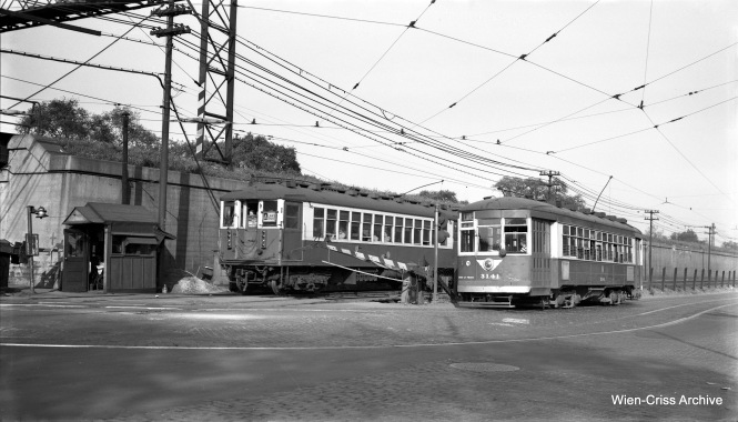"A green and cream ""L"" car passes a green and cream trolley. CTA 4327 is at the front of a Lake Street ""L"" train, running at ground level under trolley wire at Pine Street, while CTA 3141 prepares to turn and cross the tracks, heading to the other side of the Chicago & North Western embankment on September 26, 1953. (Robert Selle Photo, Wien-Criss Archive)"