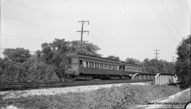 Chicago Aurora & Elgin cars 401 and 431 are crossing the DesPlaines River westbound on August 29, 1953, about a half mile west of the DesPlaines Avenue station. This is now the site of I-290. The CA&E tracks and bridge were moved north of the highway in 1959 but were never used by the interurban, which was subsequently abandoned. In this section, the CA&E ran parallel to Harrison Street, which has also been taken up by the highway. (Robert Selle Photo)