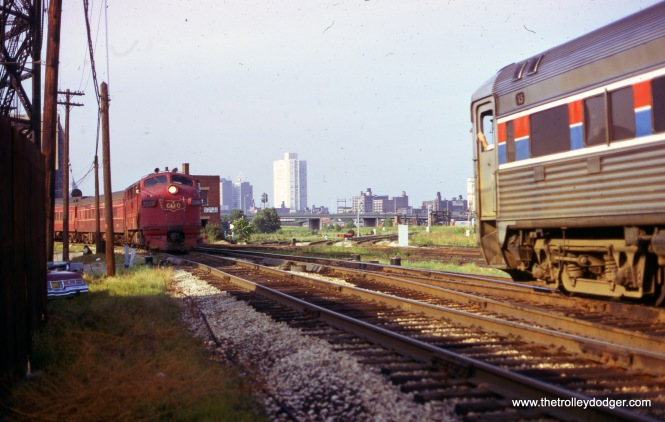 A GM&O loco heads up a passenger train in August 1975 and prepares to pass an Amtrak train. (William Shapotkin Collection)