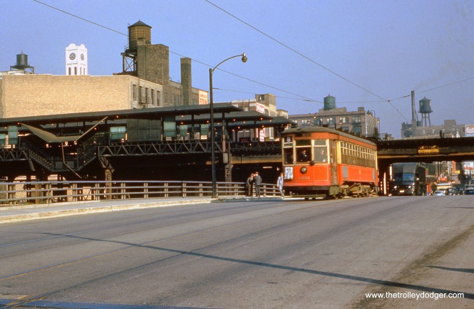 "CTA 6151 is southbound at Halsted and Congress on October 5, 1953 running on Route 8. The bridge 6151 is on spanned the Congress Expressway construction site. The highway was not yet open, and service continued on the Halsted ""L"" station at rear (with two tracks instead of the original four) until June 1958. (William Shapotkin Collection)"