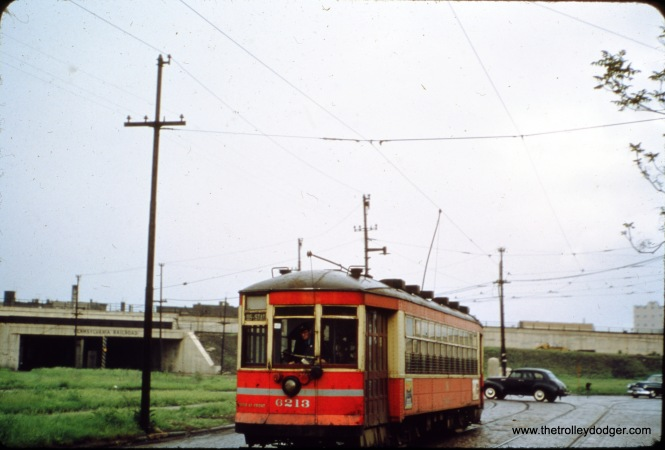 "CSL/CTA 6213 at 93rd and Exchange Avenue. The slide said the cross street was Anthony, but as Tony Waller points out, ""The photo of the red streetcar on route 95 captioned as being at 93rd and Anthony Ave. is actually at 93rd and Exchange Ave. The streetcar line westbound turned from Exchange onto 93rd. Anthony Ave. parallels the PRR/NYC viaducts (and now the Skyway bridge alignment) that is in the near distance; crossing the streetcar line at a perpendicular angle."" (William Shapotkin Collection)"