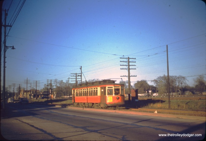 "CTA 5574 at an unknown location. Jon Habermaas writes, ""Photo appears to be on the Halsted route where the line is on private right of way along Vincennes Ave., paralleling the Rock Island mainline... in the background you can see the Washington Heights Rock Island depot and a cross buck along the Pennsy's Panhandle division, which crosses Vincennes Avenue and the Rock Island just south of 103rd Street. The car would be around 104th and Vincennes Ave."" Our resident south side expert M. E. adds, ""Mr. Habermaas's description is accurate. I will add that this private right of way started at 89th St., just south of the CRI&P Beverly branch viaduct, and ended around 107th St. where Vincennes veered farther west from the CRI&P main line. And more historically, this right-of-way originated for the Kankakee car, which had its barn at 88th and Vincennes and ran on Halsted as far north as Englewood."" Andre Kristopans: ""Car 5574 SB at 105th or so. You can just make out the 104th RI station in the back, and PRR crossbuck to the right in the distance."" (Robert W. Gibson Photo)"