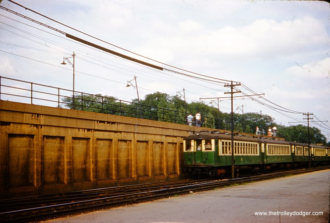 "In August 1960, a four-car train of CTA 4000-series cars heads west on the ground-level portion of the Lake Street ""L"". Since it appears there are passengers waiting for a Chicago & North Western commuter train on the adjacent embankment, I would say it's possible the location is near Marion Street in suburban Oak Park. The outer 2.5 miles of the Lake route were relocated onto the embankment in October 1962."