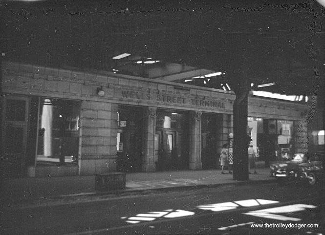 "Here's a rather unique view showing the front of the old Wells Street Terminal, or what was left of it anyway, as it appeared in 1959. This terminal was last used by the CA&E in 1953. Two years later, the upper portion of the attractive facade was removed and a new track connection was built so that Garfield Park trains could connect to the Loop ""L"". A new connection was needed, since the old one had to give way to construction on Wacker Drive. The remainder of the terminal, and the track connection, were no longer needed after the Congress rapid transit line replaced the Garfield Park ""L"" in 1958, and they were removed in 1964. Note there is a barber shop occupying part of the building."