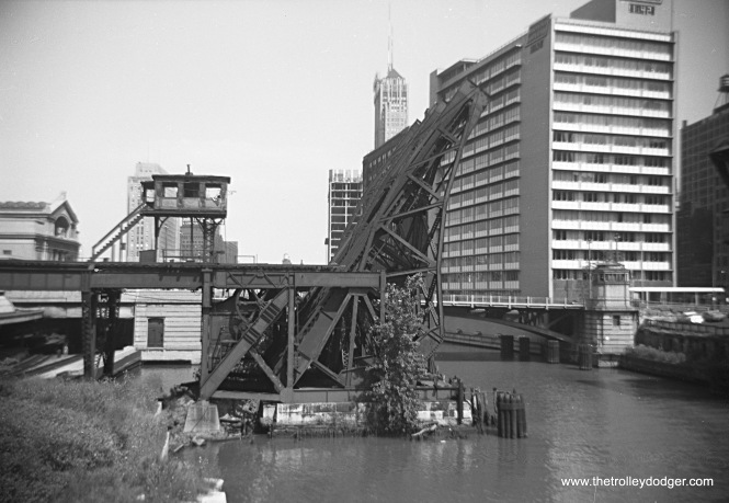 "The old Metropolitan ""L"" crossed the Chicago River just south of Union Station (just visible at left) and had four tracks, necessitating two bridges. After these tracks were taken out of service in June 1958, the bridges were permanently raised, and razed in 1964."