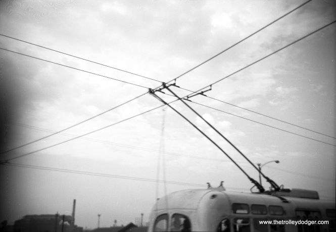 "It's not clear where this picture was taken. The two wires that cross the trolley bus wires are, I am told, ""feeder span hangers."" The last Chicago trolley bus ran in 1973. The CTA currently has two electric buses that run on batteries, and has just placed an order for 20 more."