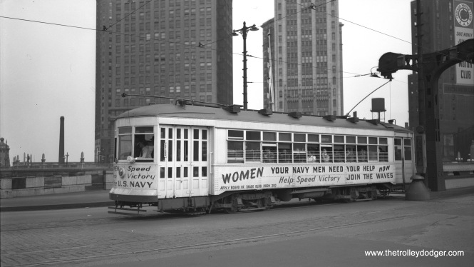 Chicago Surface Lines 1775 crosses the Chicago River at Wabash Avenue on May 30, 1945, promoting the WAVES (Women Accepted for Volunteer Emergency Service). The nearby State Street bridge was out of service from 1939 to 1949 due to subway construction and wartime materials shortages.