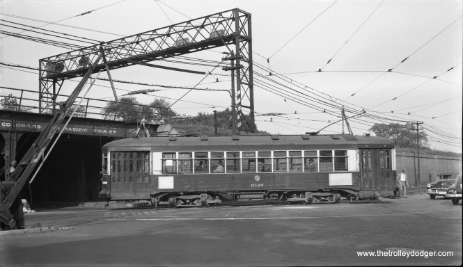 "CTA one-man car 3125, heading west on Route 16, is turning north from Lake Street onto Pine Street, where Lake takes a jog. In the process, it crosses the ground-level Lake Street ""L"". This picture was taken on September 26, 1953. (Robert Selle Photo)"