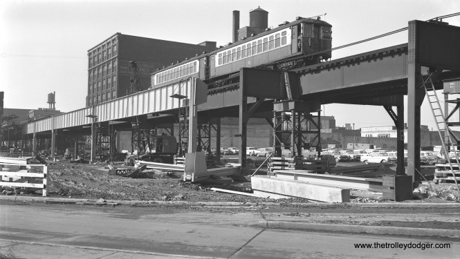 "A two-car train of 4000s is on the Lake Street ""L"" during construction of the Northwest (now Kennedy) expressway on February 25, 1958. The new highway opened in 1960. Further south, the Garfield Park ""L"" also crossed the highway footprint and had to be shored up around the same time this photo was taken. But once the new Congress rapid transit line opened on June 22, 1958 the Garfield line was no longer needed and the structure was removed where it crossed the highway, cutting the line off from the rest of the system. The remaining portions of structure west of there were removed in 1959; east of there, parts remained until 1964. The Lake Street ""L"", on the other hand, rechristened the Green Line, is still here."