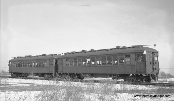 "This negative did not come with any identifying information, but it is obviously from a February 12, 1939 fantrip where the fledgling Central Electric Railfans' Association chartered Chicago Rapid Transit Company ""L"" cars 4317 and 4401 and took them out on parts of the CA&E including the Mount Carmel branch. However, since that line used overhead wire, that's not where this picture was taken. Instead, it appears to be out near the end of the line at Mannheim and 22nd Street on the CRT's lightly used Westchester line, which was built in anticipation of housing being built in this area (which did not come about until the 1950s). South of Roosevelt Road, the line was single-track, which appears to be the case here. If not for the Great Depression, more housing would have been built here. We have previously run two other pictures from the same fantrip, both taken on the Mt. Carmel branch. The CTA substituted bus service for ""L"" on the Westchester line in 1951 as it did not want to continue paying rent to the CA&E, which had already announced its intentions to truncate passenger service to Forest Park, which meant similar rent payments to the CTA were about to cease."
