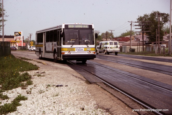 "This slide was labeled ""Oak Park,"" but actually, it's on the border between Elmwood Park and River Grove. PACE bus 22550 is heading west on Grand Avenue, going over the long crossing of the Metra Milwaukee District West Line on route 319 on May 8, 1993. There has een much talk over the years of grade-separating these tracks, where some accidents have occurred, but so far nothing has come of it. (Ronald J. Sullivan Photo)"