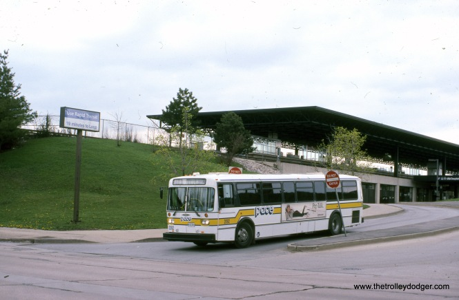 PACE bus 2092 is exiting from the CTA DesPlaines Avenue terminal in April 1992. Where the bus is, was once the approximate location of Chicago Great Western freight tracks, which spanned DesPlaines Avenue via a bridge and then connected with the Baltimore & Ohio Chicago Terminal tracks. That portion of the old CGW right-of-way between here and First Avenue has been paved, and provides a connection to the Prairie Path, which starts at First Avenue.