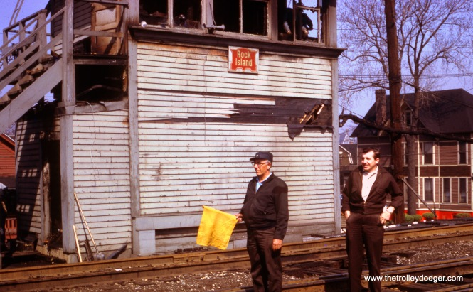 Tower man Roy Bliss and Assistant Tower man Jack Poehron are flagging all trains by the burned-out Rock Island 61st Street Tower on April 20, 1967. The wooden tower had opened in 1898.