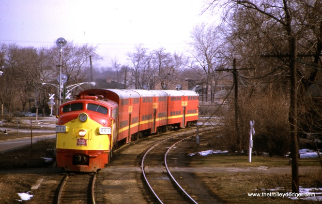 "Westbound Rock Island train #113 at the 91st Street depot on April 5, 1970. Our resident south side epert M. E. adds, ""The caption says this view is ""at the 91st Street depot."" Not quite. The view faces north. The train is curving from west (along 89th St.) to south. Notice the railroad crossing signals and gates in the background. That trackage joined with the CRI&P traffic to the east. On that trackage ran the B&O Capitol Limited on its way to Washington DC, as captured in https://thetrolleydodger.files.wordpress.com/2018/07/proofs288.jpg , although in that photo the Capitol Limited is inbound to Chicago."""
