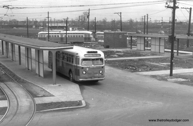 "CTA bus 6541 is at the Western and 79th loop in 1953. Meanwhile, a postwar PCC (built by the St. Louis Car Co.) goes around the loop. Streetcar service on Western ended in June 1956. Jeff Wien writes, ""The caption states that it is 1953 in this photo. I would guess 1948 not long after the loop opened. There is virtually no landscaping anywhere and the sidewalks look like they were recently laid. Later pictures of this loop showed green grass and bushes which was typical of CTA loops until they decided to asphalt over everything (ie: Clark-Arthur loop)."" Andre Kristopans: ""Bus 6541 at 79th/Western is definitely soon after loop opened. After 79th was converted, this spot is where 79th buses loaded, and 49A's loaded about three bus lengths back, on the left side of the driveway (see 2578 shot following for new location)."""