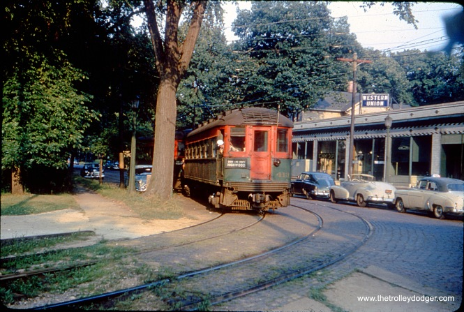 This interesting scene shows North Shore Line car 413 (and train) turning off street running on Greenleaf Avenue in Wilmette on the Shore Line Route, which uit in 1955. The building at right is still standing.
