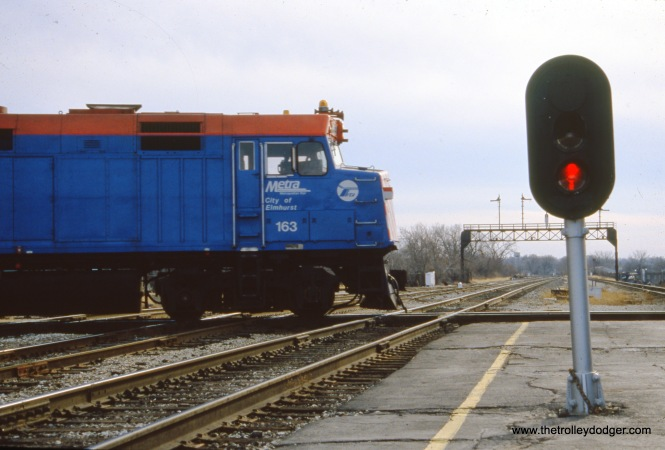 Joliet, IL: Loco 163 is seen pushing an eastbound Metra/Rock Island suburban train across the ATSF/IC (ex-ICG, former GM&O, nee C&A) diamonds at Union Station. The view looks south in December 1990. (Paul D. Schneider Photo)