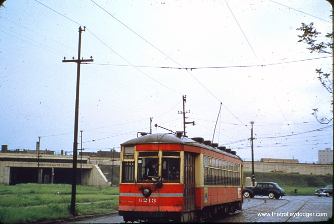 "Chicago Surface Lines 6213. Tony Waller adds, ""The photo of the red streetcar on route 95 captioned as being at 93rd and Anthony Ave. is actually at 93rd and Exchange Ave. The streetcar line westbound turned from Exchange onto 93rd. Anthony Ave. parallels the PRR/NYC viaducts (and now the Skyway bridge alignment) that is in the near distance; crossing the streetcar line at a perpendicular angle."""