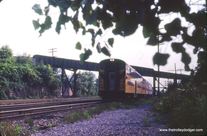 "An eastbound C&NW train is passing under the CGW bridge on July 9, 1968. Bill Shapotkin adds, ""This photo was taken in Lombard east of Grace St. Today, a Great Western Trail x/o over the UP (C&NW) at the same location. View looks west."""